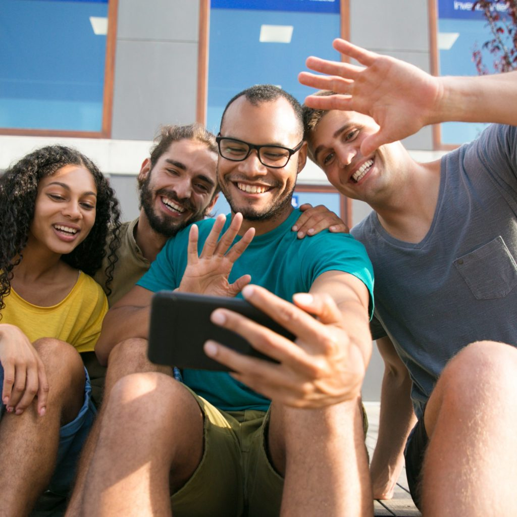 Happy friends talking to another friend through video call on mobile phone. Young men and woman sitting outside, gesturing, laughing, smiling at smartphone screen. Video chat concept